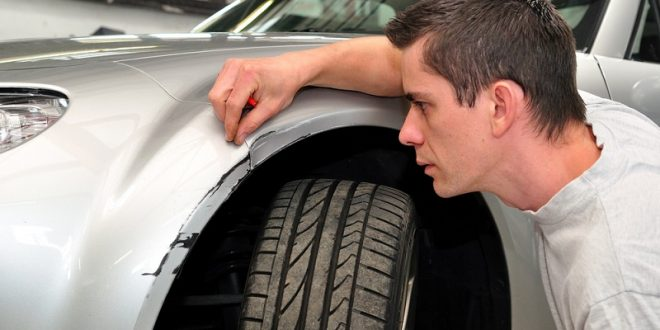 Car insurance expert, inspecting car damage.